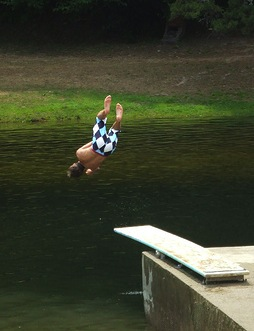 Boy dive bombing into river from spring board
